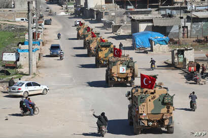 FILE - A column of armored Turkish military vehicles drives on a patrol along a road in the de-militarized zone in Syria's northern Idlib province near the town Saraqib, March 8, 2019.