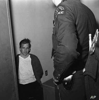 Lee Harvey Oswald sits in police custody shortly after being arrested for assassinating President John F. Kennedy in Dallas, Texas, Nov. 22, 1963.