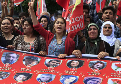 FILE - Mourners chant slogans as they carry a banner with pictures of victims of an explosion in Suruc, southeastern Turkey, during a protest in Istanbul, July 22, 2015. The suicide bombing, which killed 32 people and wounded scores, is part of a ret...