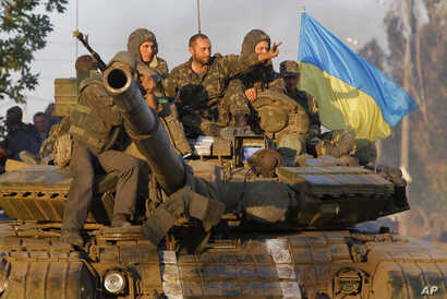 Soldiers of Ukrainian army ride on a tank in the port city of Mariupol, southeastern Ukraine, Sept. 5, 2014.