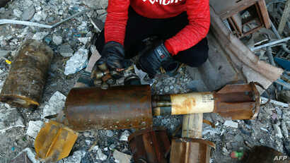 A Syrian man shows remnants of rockets reportedly fired by regime forces on the rebel-held besieged town of Douma in the eastern Ghouta region on the outskirts of the capital Damascus, Jan. 22, 2018.