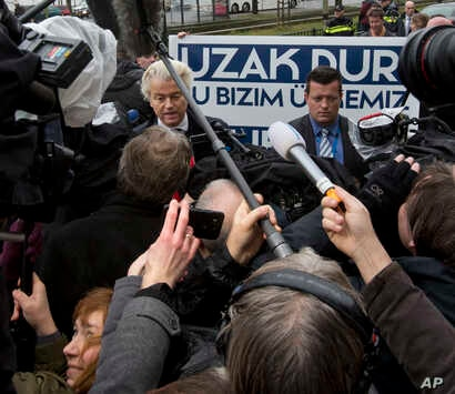 """Campaign staff hold a banner reading """"Stay Away, This Is Our Country"""" as firebrand anti-Islam lawmaker Geert Wilders, left, protests outside the Turkish embassy in The Hague, Netherlands, March 8, 2017, against the planned campaign visit of Turkish F..."""