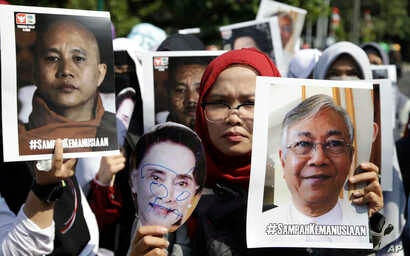 "Muslim women hold posters of Wirathu, the leader of Myanmar's nationalist Buddhist monks, Myanmar's State Counsellor Aung San Suu Kyi, and President Htin Kyaw, with writings that read ""The waste of humanity"" during a rally against persecution of Rohi..."