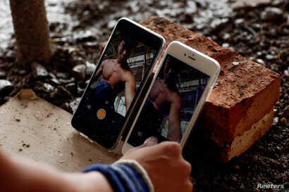FILE - Shi Shenwei sets up his phones to record a high bar routine at the construction site of a Buddhist temple in the village of Huangshan, in Fujian Province, China, on September 28, 2016.