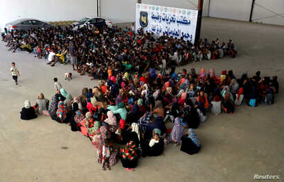 Migrants are seen in a shelter after they were relocated from government-run detention centers,
