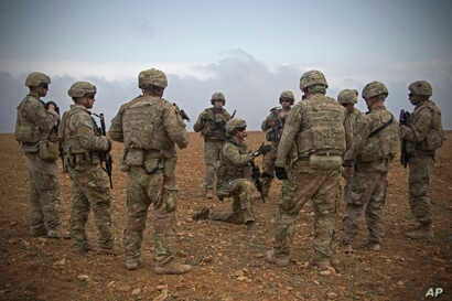 In this Nov. 7, 2018, photo released by the U.S. Army, U.S. soldiers gather for a briefing during a combined joint patrol rehearsal in Manbij, Syria.