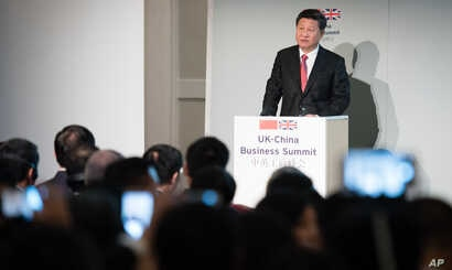 """FILE - China's President Xi Jinping addresses guests and delegates at the UK-China Business Summit in Mansion House, central London, Oct. 21, 2015. Britain will be China's """"partner of choice"""" in the West, Prime Minister David Cameron declared as part..."""