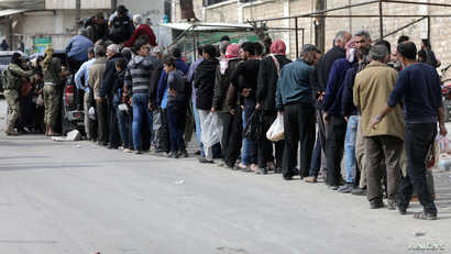 People stand in a queue to get bread in Afrin, Syria, March 20, 2018.