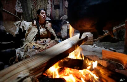 In this Nov. 15, 2018, photo, Mashpee Wampanoag Kerri Helme, of Fairhaven, Mass., uses plant fiber to weave a basket while sitting next to a fire at the Wampanoag Homesite at Plimoth Plantation, in Plymouth, Mass.