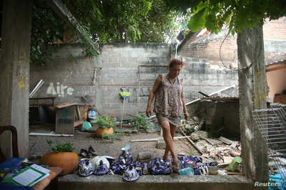 Felina, 50, an indigenous Zapotec 'muxe,' walks on the crockery inside her house destroyed after an earthquake in Juchitan, Sept. 10, 2017.