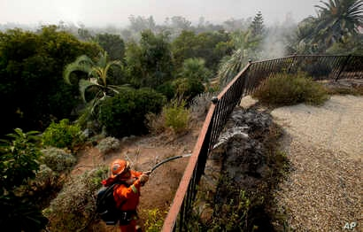 A firefighter from the California Conservation Crops Alder Camp works to put out wildfire hot spots, Dec. 16, 2017, in Montecito, Calif.