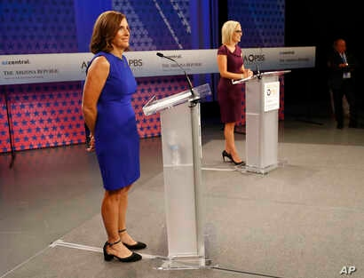 U.S. Rep. Martha McSally, R-Ariz., left, and U.S. Rep. Kyrsten Sinema, D-Ariz., prepare their remarks in a television studio prior to a televised debate, Oct. 15, 2018, in Phoenix. They're running for the U.S. Senate seat being vacated by Republican ...