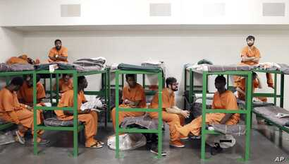FILE - Inmates hang out on their bunks in the Harris County Jail in Houston, Texas.