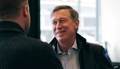 Former Democratic Colorado Governor John Hickenlooper talks with AmeriCorps members prior to a roundtable campaign stop in Manchester, N.H., March 22, 2019.