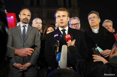 French President Emmanuel Macron speaks as Prime Minister Edouard Philippe and Archbishop of Paris, Michel Aupetit, stand near the Notre Dame Cathedral where a fire burns in Paris, France, April 15, 2019.