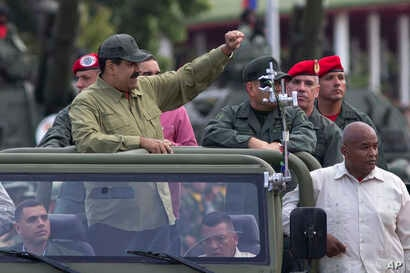FILE - Defense Minister Vladimir Padrino Lopez, center right, face obscured, and Gen. Ivan Hernández, standing behind Padrino Lopez, head of both the presidential guard and military counterintelligence, accompany Venezuela's President Nicolas Maduro...