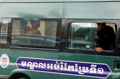 Yeang Sothearin and Uon Chhin, former journalists for U.S. founded Radio Free Asia (RFA), who have been charged with espionage, sit inside a police vehicle as they arrive for a bail hearing at the Appeals Court in Phnom Penh, Cambodia, April 19, 2018...