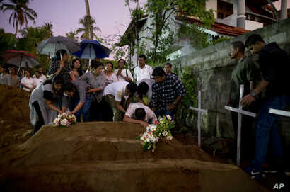 Relatives place flowers after the burial of three victims of the same family, who died at Easter Sunday bomb blast at St. Sebastian Church in Negombo, Sri Lanka, April 22, 2019.