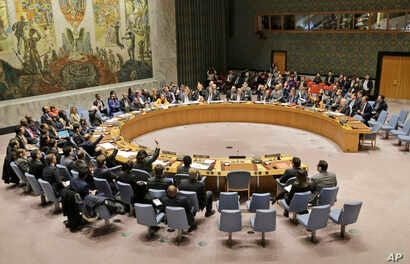 FILE - Members of the United Nations Security Council vote on a resolution during a meeting at U.N. headquarters, Feb. 28, 2019.