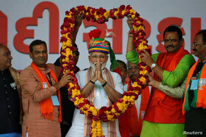 India's Prime Minister Narendra Modi gestures as he is presented with a garland during an election campaign rally in Himmatnagar, Gujarat, India, April 17, 2019.