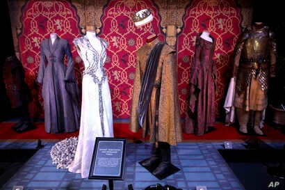 FILE - In this April 10, 2019, file photo costumes of the characters Joffrey Baratheon and Margaery Tyrell on display during the launch of The Game of Thrones Touring Exhibition at the Titanic Exhibition centre in Belfast, Northern Ireland.