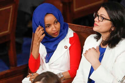 FILE - Rep. Ilhan Omar, D-Minn., left, joined at right by Rep. Rashida Tlaib, D-Mich., listens to President Donald Trump's State of the Union speech, at the Capitol in Washington.