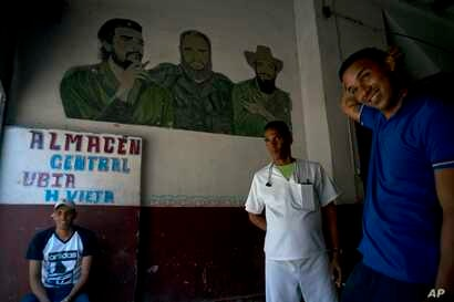 "Men take a break inside a warehouse featuring a mural of revolutionary leaders Camilo Cienfuegos, right, Ernesto ""Che"" Guevara, left, and Fidel Castro, in Havana, Cuba, April 17, 2019."