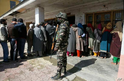 An Indian paramilitary soldier stands guard as Kashmiri voters wait in a queue to cast their votes outside a poling station during the second phase of India's general elections, on the outskirts of Srinagar, Indian controlled Kashmir, April 18, 2019....