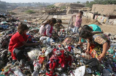 Pakistan children sort through garbage for recycleable items to sell, at a dump in Karachi, April 4, 2019.