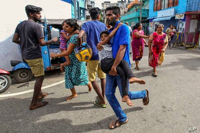Sri Lankans living near St. Anthony's shrine run for safety after police found explosive devices in parked vehicle, which later exploded in Colombo, April 22, 2019.