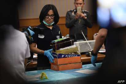 FILE - An employee from the Department of Special Investigation sorts through evidence from a massage parlor after police raided the premises because of suspicions of underage trafficking and prostitution, in Bangkok, Jan. 15, 2018.