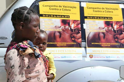 A woman and her baby walk past cholera vaccination campaign posters on the first day of the cholera vaccination program at a camp for displaced survivors of cyclone Idai in Beira, Mozambique, April, 3, 2019.