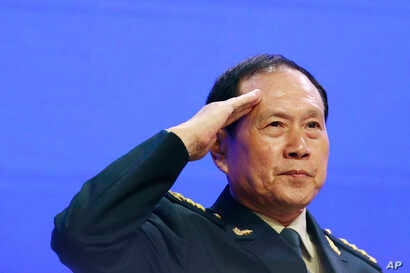 Chinese Defense Minister Gen. Wei Fenghe salutes attendees ahead of the fourth plenary session of the 18th International Institute for Strategic Studies Shangri-la Dialogue, an annual defense and security forum in Asia, in Singapore, June 2, 2019.