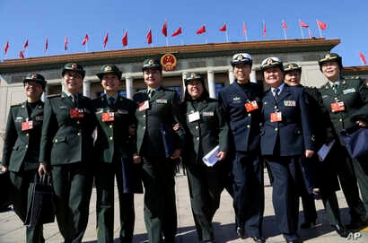 Chinese women delegates walk together to pose outside the Great Hall of the People after attending a plenary session of the Chinese People's Political Consultative Conference (CPPCC) in Beijing, Thursday, March 8, 2018.