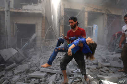 A man evacuates a young bombing casualty after a reported air strike by regime forces and their allies in the jihadist-held Syrian town of Maaret Al-Noman in the southern Idlib province, on May 26, 2019.