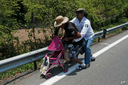 A Central American migrant pushing a child in a baby carriage is detained by a Mexican immigration agent from behind on the highway to Pijijiapan, Mexico, April 22, 2019.