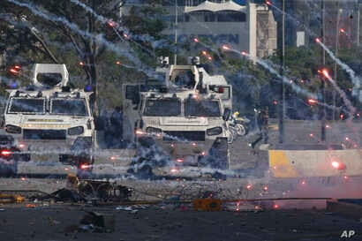 Fireworks launched by opponents of Venezuela's President Nicolas Maduro land near Bolivarian National Guard armored vehicles loyal to Maduro, during an attempted military uprising in Caracas, Venezuela, Tuesday, April 30, 2019.