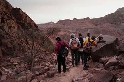 Tourists stop to look at the scenery on a trek in the mountains near Wadi Sahw led by Beduin women, Abu Zenima, in South Sinai, Egypt, March 29, 2019.