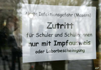 A sign at the entrance a school in Freiburg, southern Germany,  April 11, 2008, instructs that only vaccinated children are allowed to attend classes.