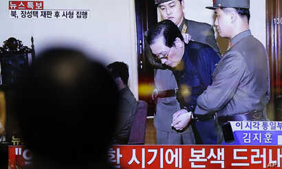 FILE - A man watches a live TV news program showing North Korean leader Kim Jong Un's uncle Jang Song Thaek, second from right, being escorted by military officers during a trial in Pyongyang, North Korea, Dec. 12, 2013. North Korea said it had execu...