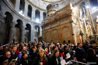 Christian worshipers attend Easter Sunday Mass in Jerusalem's Holy Sepulcher Church, April 21, 2019.