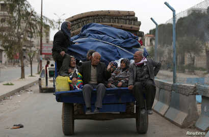 FILE - People ride in a truck with their belongings in the center of Afrin, Syria, March 24, 2018.