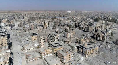 FILE - An image made from drone video shows damaged buildings in Raqqa, Syria, Oct. 19, 2017.