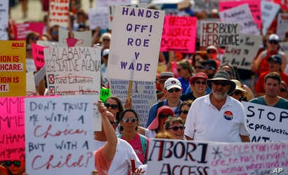 Protesters for women's rights march to the Alabama Capitol to protest a law passed last week making abortion a felony in nearly all cases with no exceptions for cases of rape or incest, May 19, 2019, in Montgomery, Ala.
