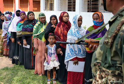 A girl looks at an armed security person standing guard as her mother waits in a queue to cast her vote outside a polling station during the sixth phase of general election in Sepahijala district in the northeastern state of Tripura, India, May 12, 2...