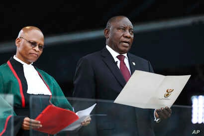 South African President Cyril Ramaphosa, right, takes the Oath of Office alongside Chief Justice, Mogoeng Mogoeng, left, at the Loftus Versfeld stadium in Pretoria, South Africa, May 25, 2019.