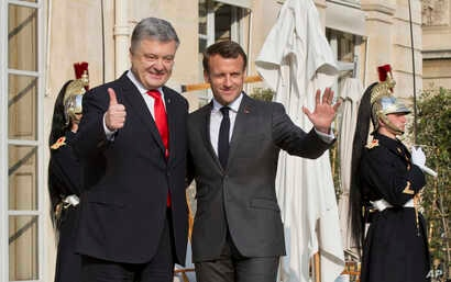 Ukraine's President Petro Poroshenko, left, is welcomed by French President Emmanuel Macron at the Elysee Palace in Paris, France, April 12, 2019.