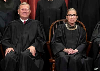 Justice Ruth Bader Ginsburg with Chief Justice John Roberts during a formal group portrait at the Supreme Court in Washington, Nov. 30, 2018.
