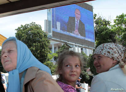 People wait for a boat next to an electronic screen showing live nationwide broadcasted call-in attended by Russian President Vladimir Putin, at Artillery Bay in the Black Sea port of Sevastopol, Crimea, June 15, 2017.