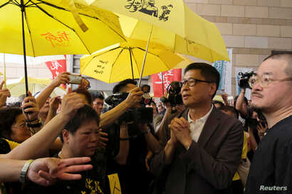 """Occupy Central pro-democracy movement founder Chan Kin-man (2nd R)  greets supporters as he arriving at the court for sentencing on his involvement in the Occupy Central, also known as """"Umbrella Movement"""", in Hong Kong, Apr. 24, 2019."""